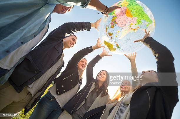 Group of people holding a world globe