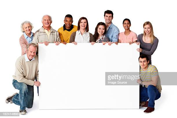 Group of people holding blank notice board