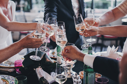 Group of people holding champagne glasses and toasting at wedding reception outdoors in the evening. Family and friends clinking glasses and cheering with alcohol at delicious feast celebration 1161568093