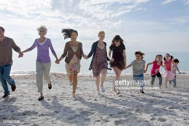 group of people holding hands and running on beach - さまざまな年齢層 ストックフォトと画像
