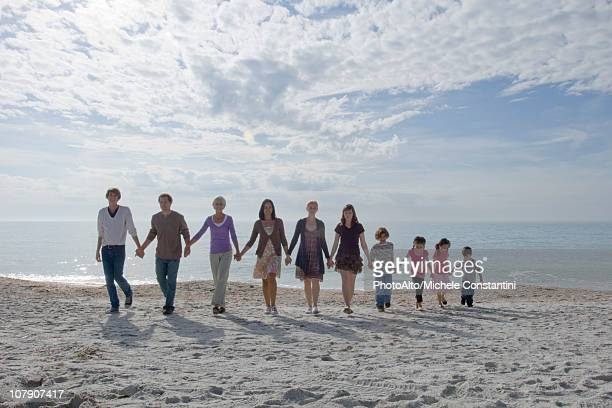 group of people holding hands and walking together on beach - さまざまな年齢層 ストックフォトと画像