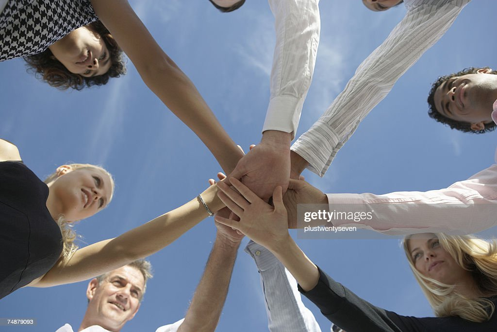 Group of people holding hands in circle, low angle view : Stock Photo