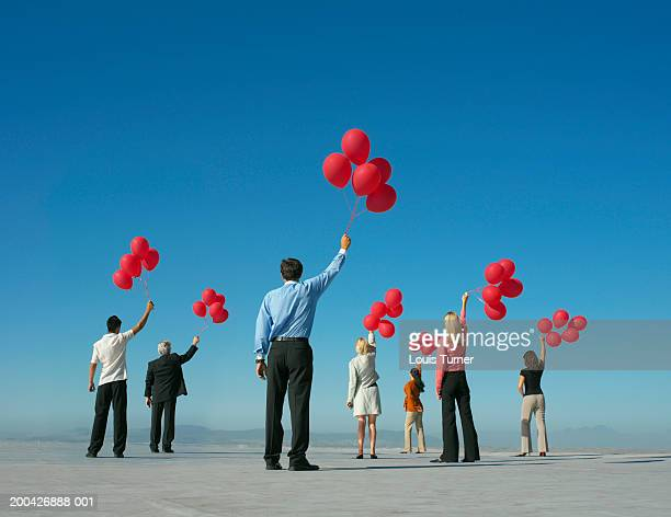 Group of people holding red balloons above heads outdoors, rear view