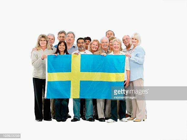 Group of people holding the Swedish flag