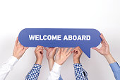 Group of people holding the WELCOME ABOARD written speech bubble