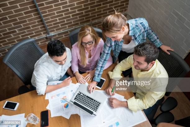 group of people in a business meeting working on a laptop computer - customer engagement stock pictures, royalty-free photos & images