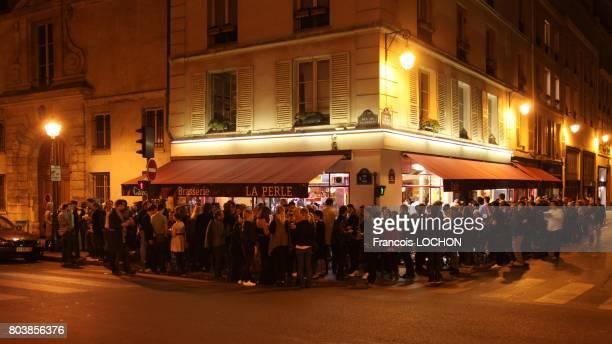 Group of people in a cafe restaurant Brasserie 'La Perle', in la Perle street, in Paris, France, circa 2000.