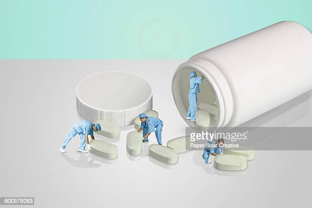 group of people in a lab looking at giant pills