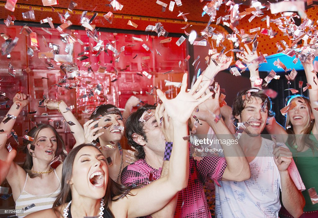 Group of people in a nightclub partying and throwing confetti : Stock Photo