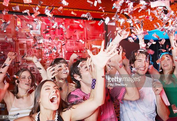 Gruppe von Menschen in der Diskothek Partys und werfen Konfetti