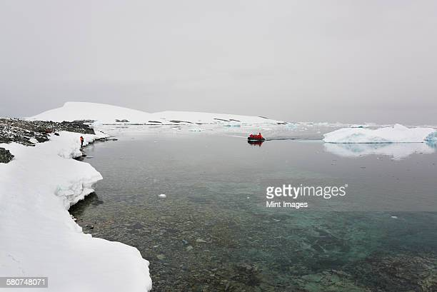 Group of people in a rubber boat moving towards the shore in the Antarctic ocean, past an ice floe.