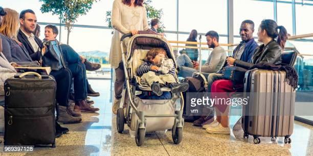 group of people in airport waiting room - toddler at airport stock pictures, royalty-free photos & images