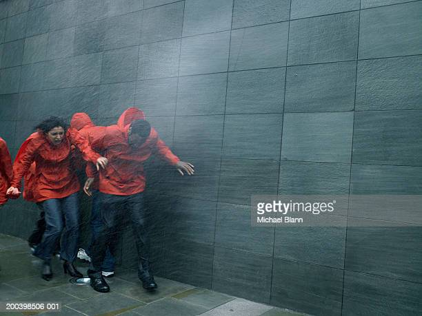 group of people in anoraks struggling to walk against rainstorm - gale stock photos and pictures