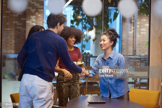 group of people in board room shaking hands - creative occupation stock pictures, royalty-free photos & images