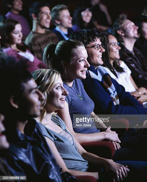 Group of people in cinema, laughing, close-up (focus on woman in centre)