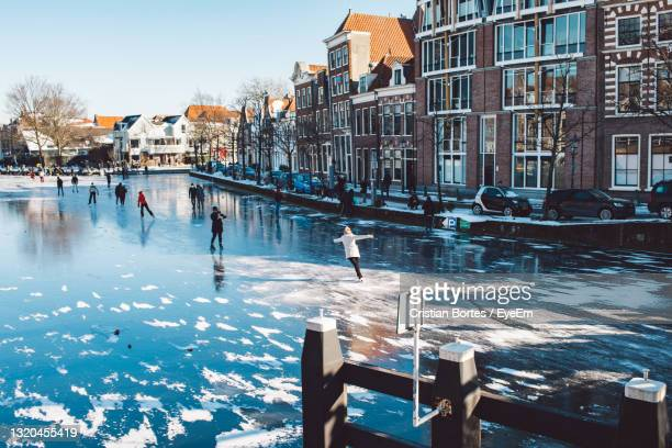 group of people in city by buildings during winter on a river - bortes stock pictures, royalty-free photos & images