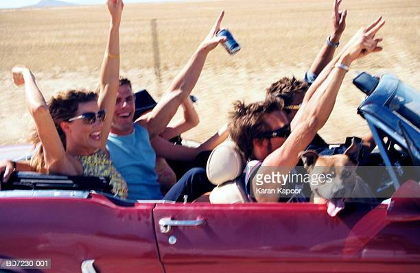 Group of people in convertible, arms in the air, close-up