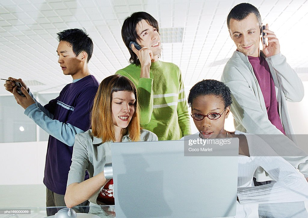 Group of people in focus, rear view of computer screen in foreground : Stockfoto