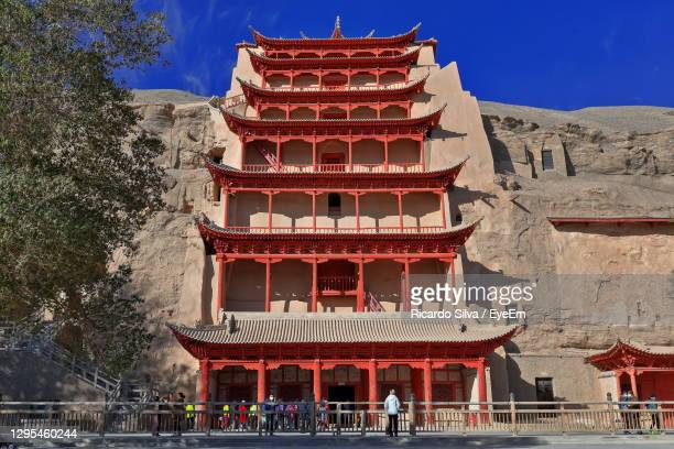 group of people in front of ancient building - gansu province stock pictures, royalty-free photos & images