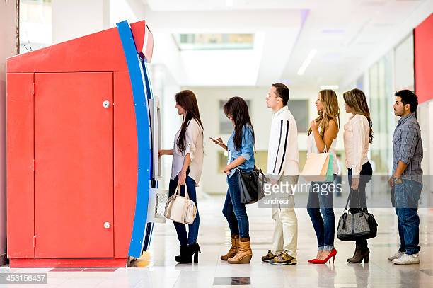 group of people in line for the atm - lining up stock pictures, royalty-free photos & images
