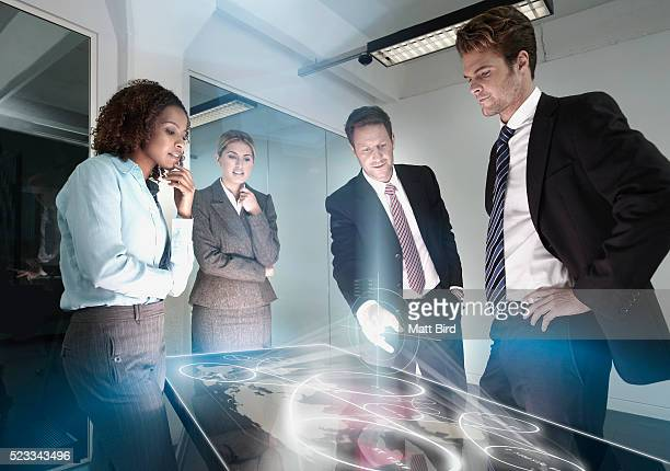 Group of people in meeting using futuristic touch screen table