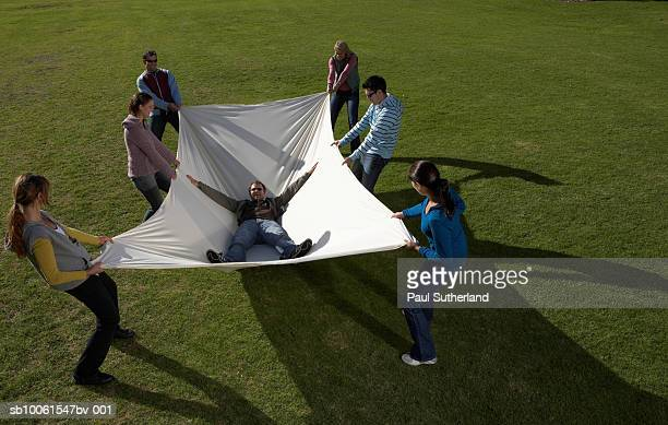 group of people in park holding large white sheet with man lying inside - catching stock pictures, royalty-free photos & images