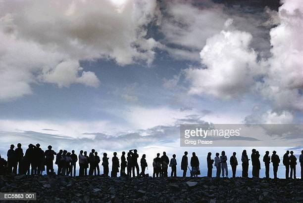 Group of people in queue on cliff