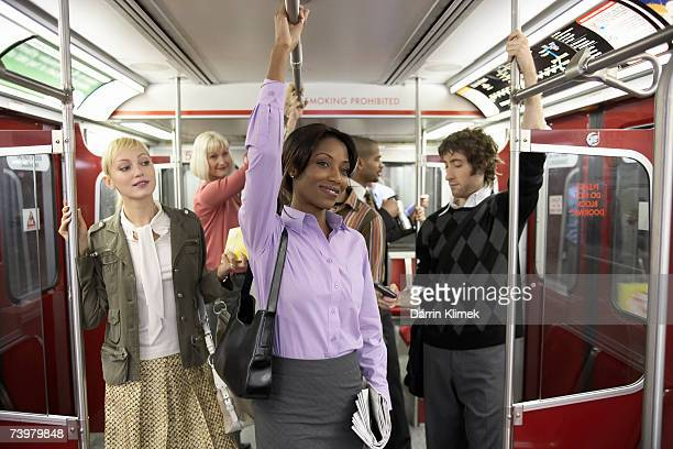 Group of people in subway train, holding onto railings