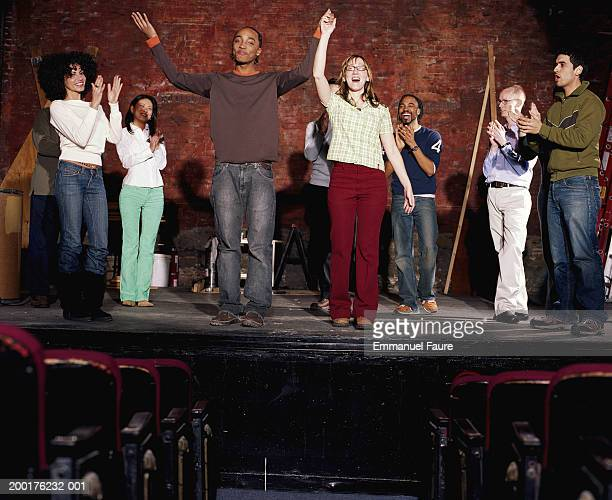 Group of people in theater applauding actors
