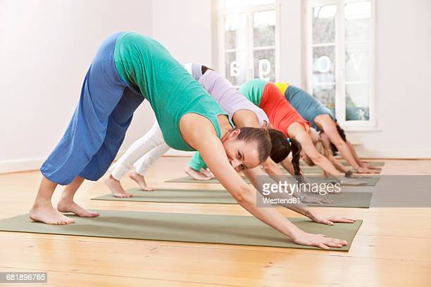 Group of people in yoga studio holding down dog pose