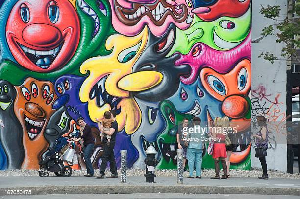 Group of people including couple with toddler and stroller in front of the Kenny Scharf mural on the corner of Houston and the Bowery in the Lower...