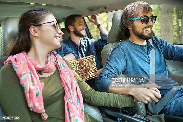 A group of people inside a car, on a road trip.