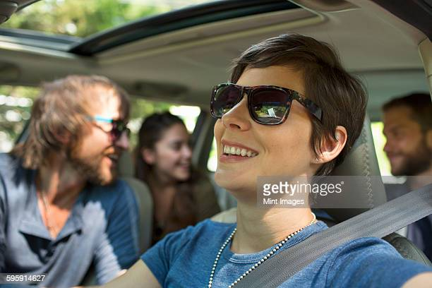 A group of people inside a car, on a road trip. View to the back seat, four passengers.
