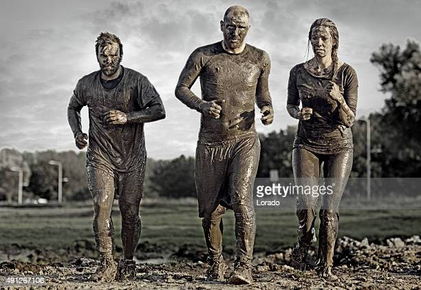 group of people jogging in mud - obstacle course stock photos and pictures