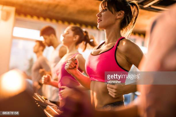 group of people jogging on treadmills in a health club. - breast stock pictures, royalty-free photos & images