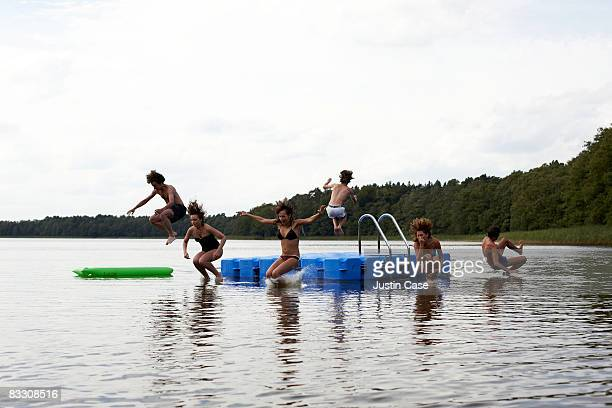 Group of people jumping off pontoon into lake
