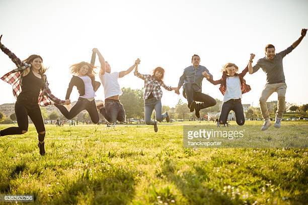 Group of people jumping on the park at dusk