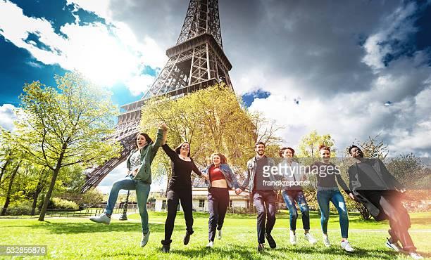 Eine Gruppe von Menschen springen im Park unter Tour Eiffel