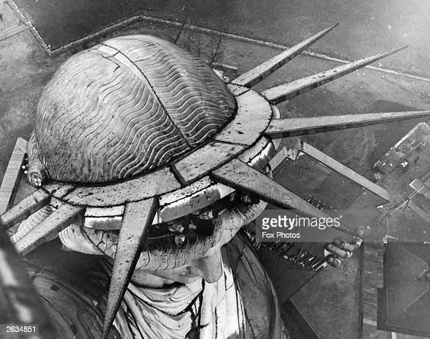 A group of people leaning out of the head of the Statue of Liberty in New York seen from the torch above
