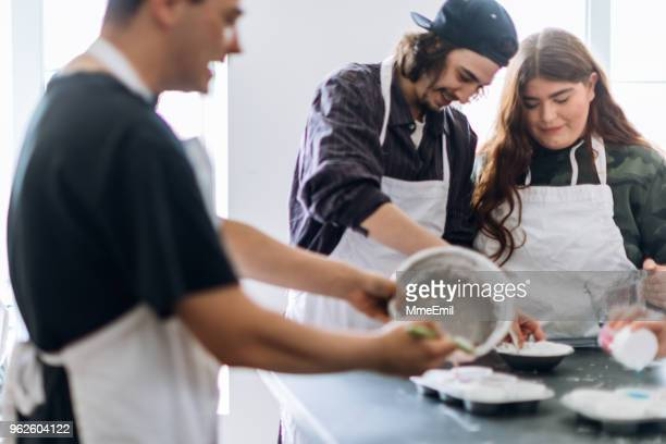 group of people learning to cook in a community center workshop - community centre stock pictures, royalty-free photos & images