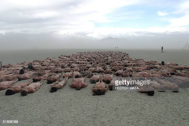 A group of people lie on the ground for a community nude picture by a fashion photographer at the Black Rock City's playa during the Burning Man...