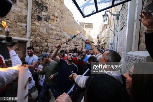 Group of people light candles of citizens who stayed at their houses, with the Holy Fire brought from the Church of the Holy Sepulchre in East...
