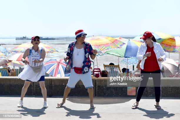 Group of people line dance on the promenade as crowds gather to enjoy the warm sunny weather on Jubilee beach on July 18, 2021 in Southend-on-Sea,...