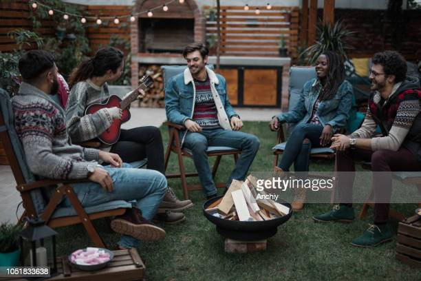 Group of people listening to a friend playing guitar