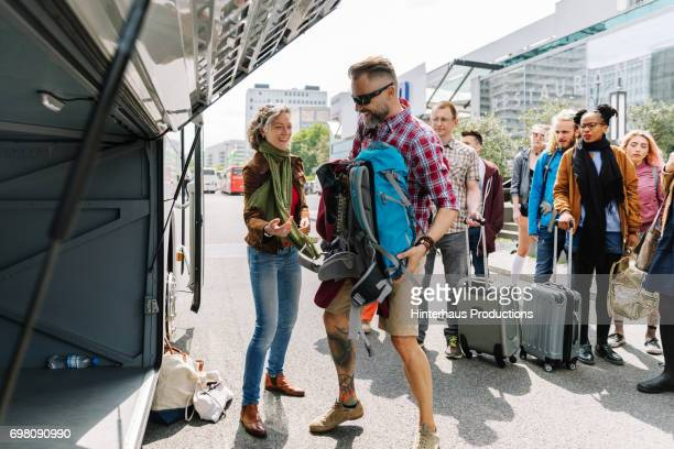 Group Of People Loading Their Baggage Onto A Coach