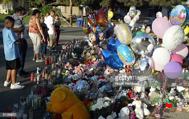 A group of people look at a memorial in front of the home of Marcus Wesson on March 18 2004 in Fresno California Wesson's arraignment on charges he...