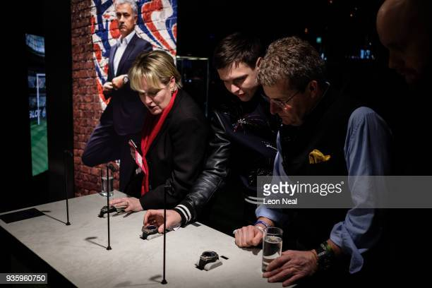 A group of people look at the new Hublot 'Big Bang Referee 2018 FIFA World Cup Russia' smart watch at the BaselWorld watch fair on March 21 2018 in...