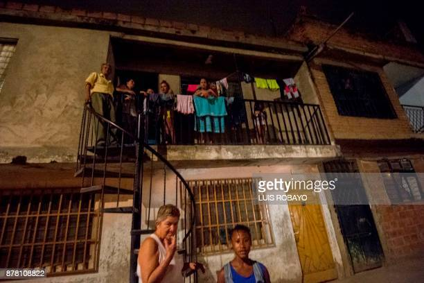 A group of people look from the balcony of a house in the Vallado neighborhood during a police security operation on November 12 in Cali Colombia...