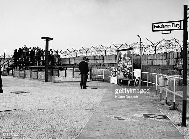 A group of people look over the Berlin Wall dividing the east and west halves of the city from the west side at Potsdamer Platz in 1966 The wall came...