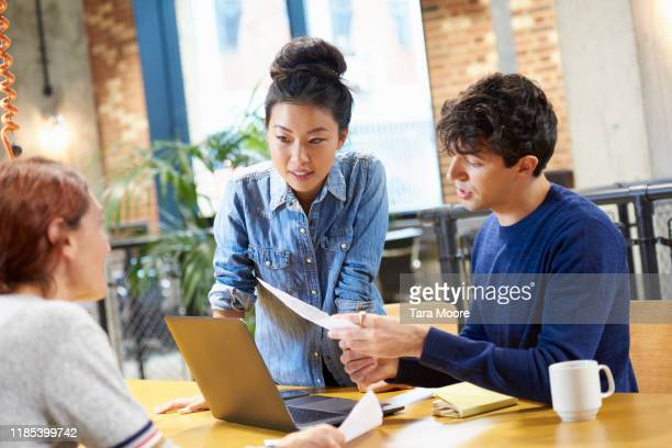 group of people looking at laptop in office - east asian ethnicity stock pictures, royalty-free photos & images